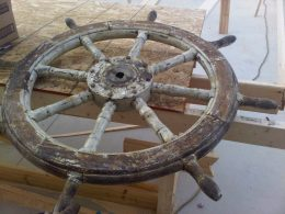 The ship's wheel in the process of being restored.