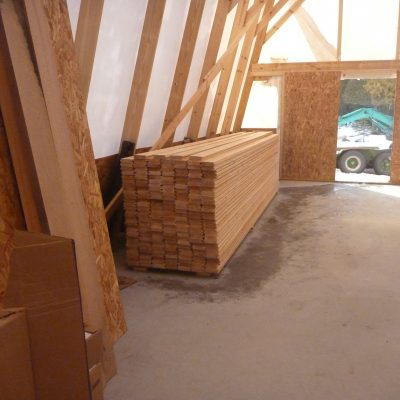 """Over 200 2"""" x 6"""" sixteen foot boards of Douglas fir acclimate and wait to be used for planking."""