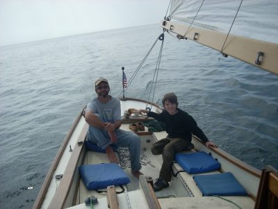 Capt. Hugh and friend at the helm.