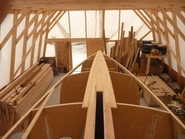 Starter planks are fitted in place forward to the bow and around the centerboard trunk