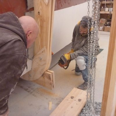 Bruce MacGregor watches Capt Hugh do some chainsaw carpentry on the framing.