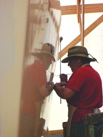 John Grenier at work painting Huron Jewel's name on the transom.