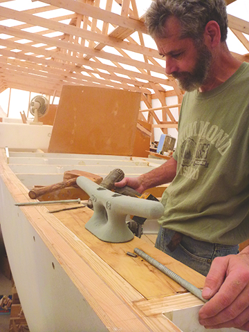 Capt. Hugh lays out the osage orange backing block for the stern cleats.