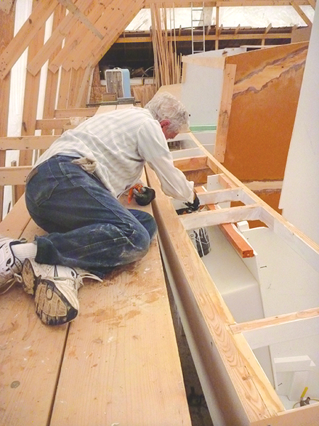 Alan Hosler finishs painting deck beams prior to decking the boat.