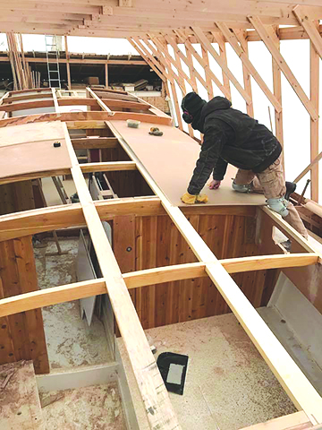 Capt Hugh lays down the first layer of plywood on top of the cabintop beams.