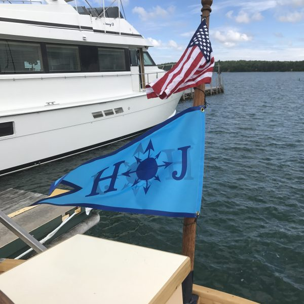 The jackstaff flys the ensign and ship's pennant.