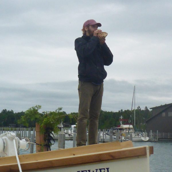 Deckhand Daniel Cox blows the conch horn to gather the crowd for the christening ceremony.