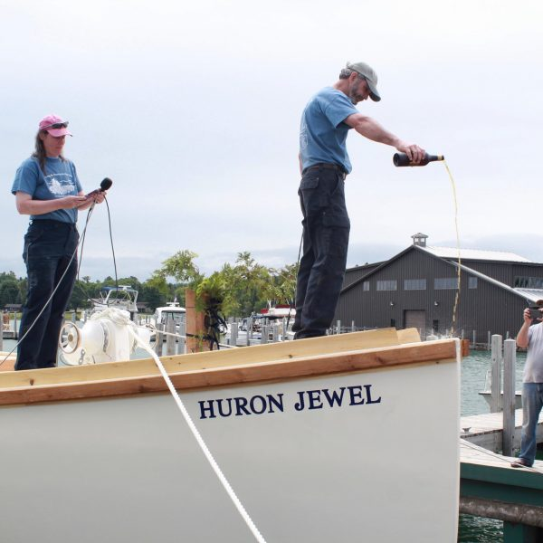 Julie Covert looks on as Capt. Hugh Covert christens Huron Jewel with 15 old year rum.